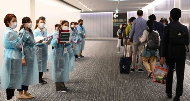 Airport operations crew for the Tokyo 2020 wait for Olympic athletes and officials arriving on a flight from Doha at Narita international airport in Narita, Chiba prefecture. Photograph: Kazuhiro Nogi/AFP via Getty Images
