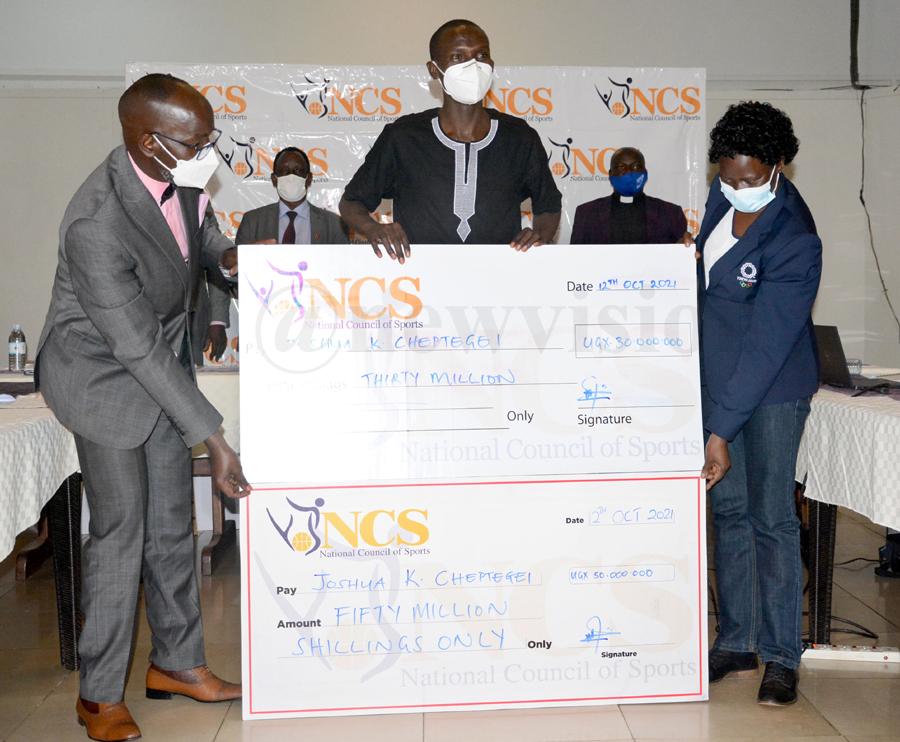 Uganda Olympic gold and silver medalist Joshua Cheptegei (center) receives sh80m dummy cheques from the Minister of State for Sport Denis Obua (left) and the Chef De Mission Beatrice Ayikoru (right) for his perfomance at the Tokyo Olympics, at NCS, October 12, 2021. Photos by Michael Nsubuga